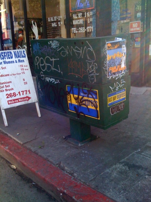 Nearly every newspaper case is covered in graffiti.